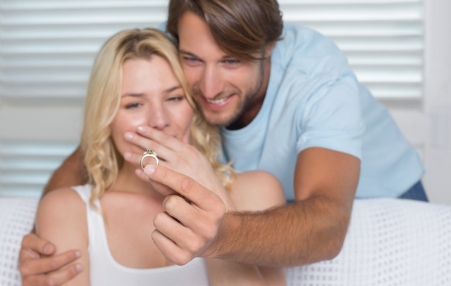 Handsome man proposing marriage to his surprised girlfriend at home in the living room