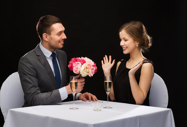 smiling man giving flower bouquet to woman