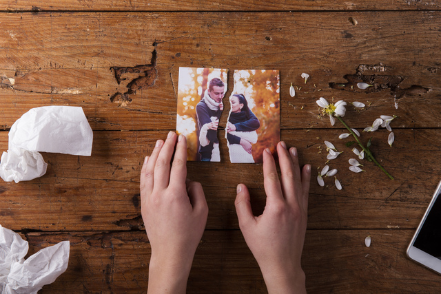 Unrecognizable sad woman holding torn picture of couple in love.