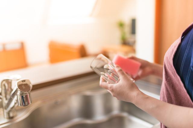 キッチンで水仕事をする20代〜30代の若い主婦