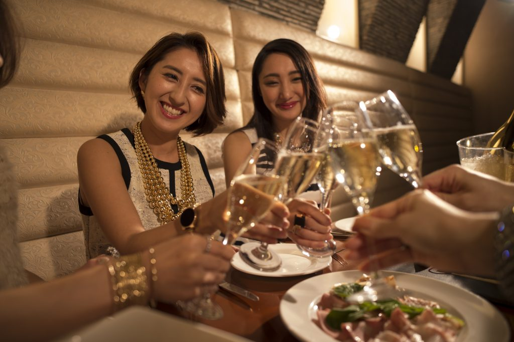 Women are toast with champagne in the restaurant